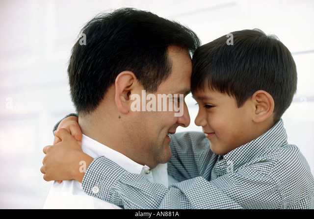 Portrait of 6 year old Mexican American boy hugging his 38 year old MexicanAmerican father - Stock Image