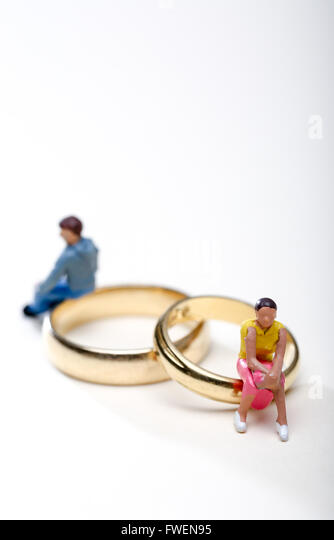 Concept image of a couple sat on wedding rings to illustrate divorce and separation - Stock-Bilder