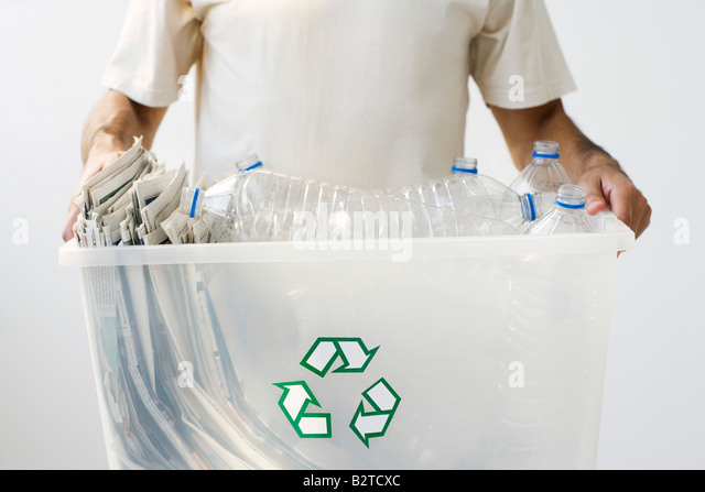 Man carrying recycling bin filled with plastic bottles and newspaper, cropped - Stock Image
