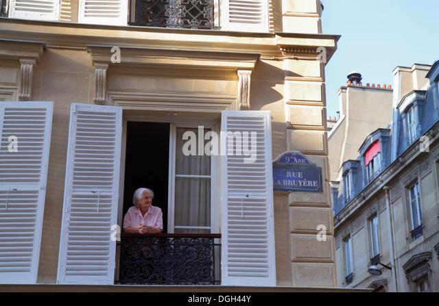 Paris France Europe French 9th arrondissement Rue La Bruyere senior woman window shutters historic Haussmann apartment - Stock Image