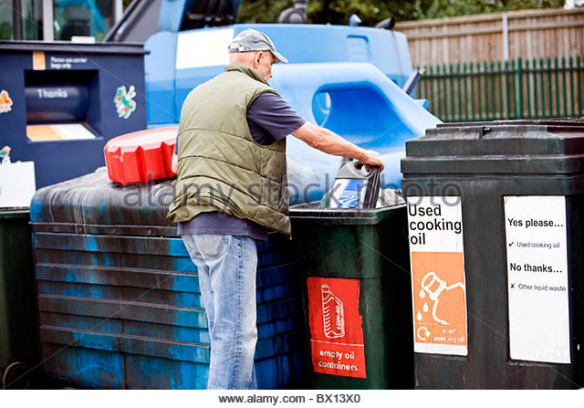 A senior man recycling an empty oil container - Stock-Bilder