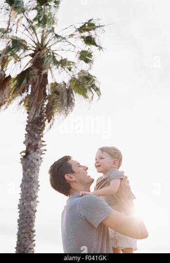 Smiling man standing by a palm tree, carrying his young son in his arms. - Stock Image