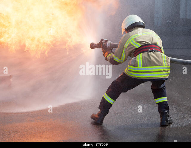 Firefighter fighting fire during training - Stock Image