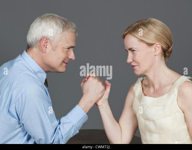 Mature couple arm wrestling - Stock Image