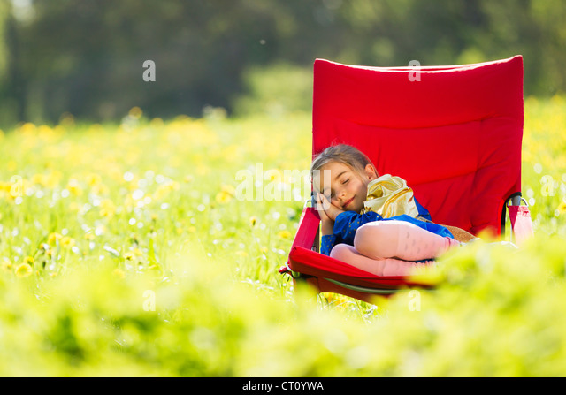 Girl in costume sleeping in chair - Stock Image