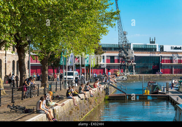 People sitting on dockside at St Augustine's Reach in Bristol Harbour, Bristol, England. - Stock Image