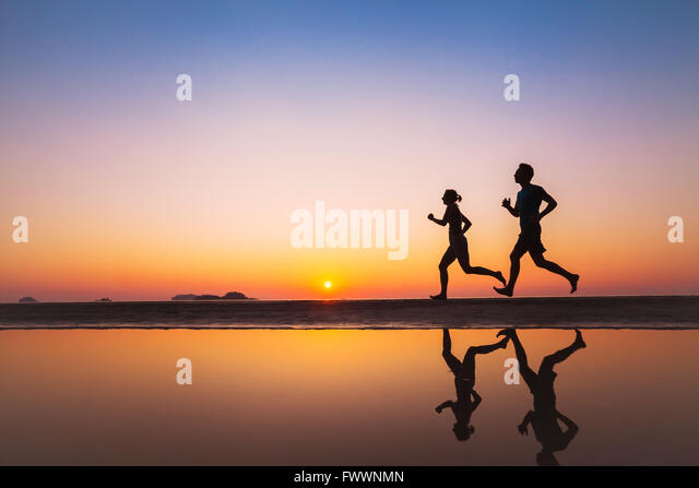 workout, silhouettes of two runners on the beach at sunset, sport and healthy lifestyle background - Stock-Bilder