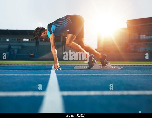 Male athlete on starting position at athletics running track. Runner practicing his sprint start in athletics stadium - Stock Image