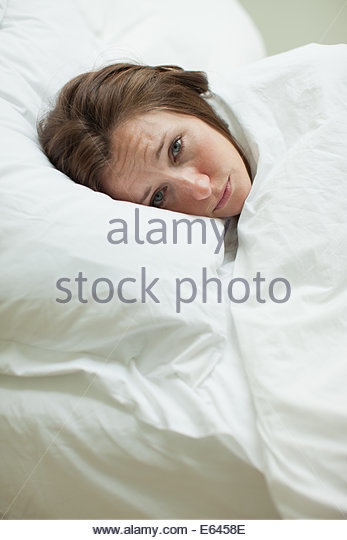Sick woman laying in bed under blanket - Stock Image