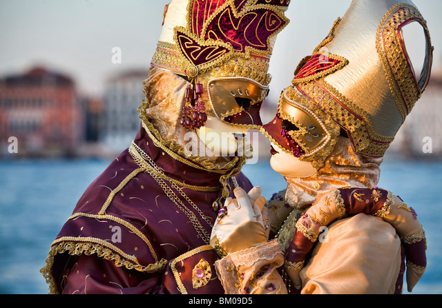 Couple wearing costumes embracing at Carnival in Venice, Italy - Stock Image