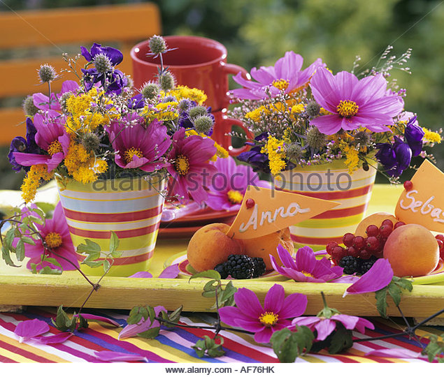 Colourful flower arrangements & plates of fruit with place-cards - Stock Image