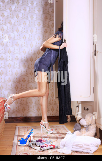 young woman near sliding-door wardrobe with bed linen - Stock Image