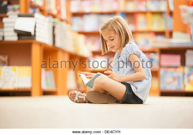 Girl sitting on floor of library with book - Stock-Bilder
