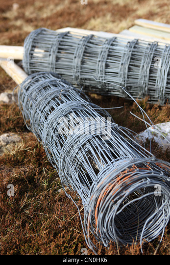 Rolls of wire fencing lying on a hillside for fencing fields. - Stock Image