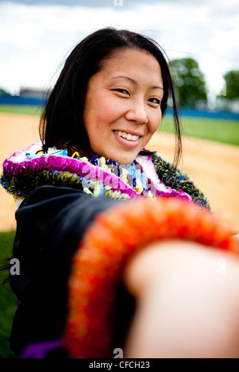 A graduate shows a Hawaiian Lei (lay) on her wrist. - Stock Image