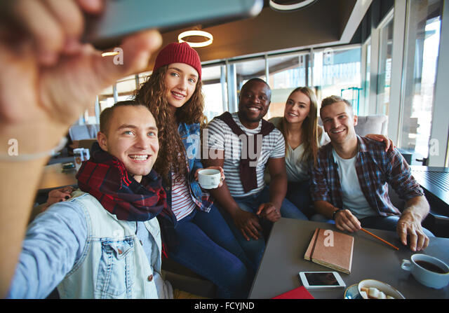 Teenage friends making selfie while gathering in cafe - Stock Image