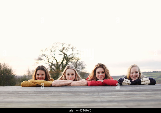 Four teenage girls in a row on patio - Stock Image