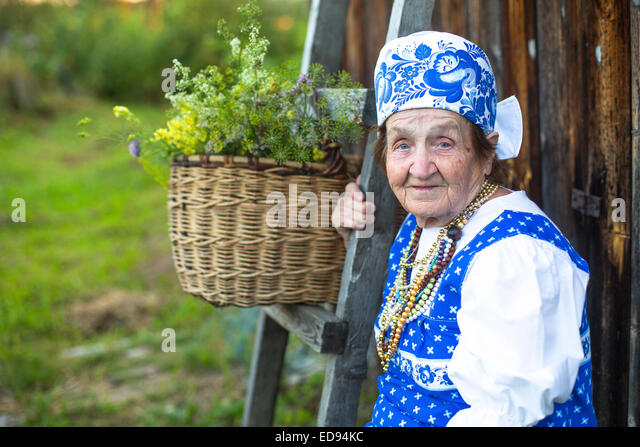 Grandmother in the village on the bench. - Stock Image
