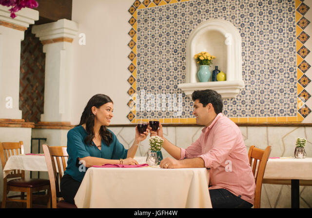 Hispanic couple toasting with wine in restaurant - Stock Image