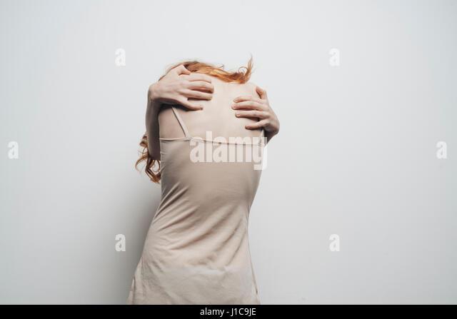 Caucasian woman hugging shoulders - Stock Image
