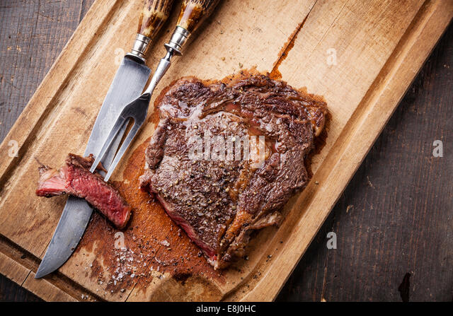 Medium rare grilled Beef steak Ribeye with knife and fork for meat on cutting board on dark wooden background - Stock Image