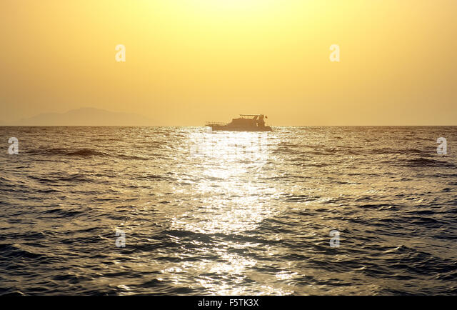 Boat in red sea at the sunset - Stock Image
