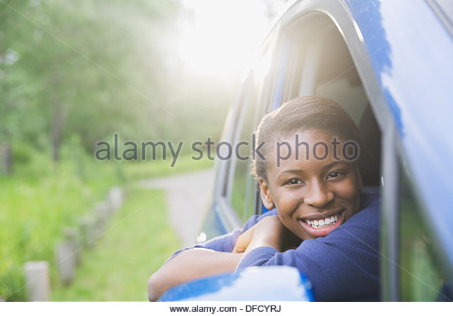 Smiling teenage girl looking out of car window - Stock Image