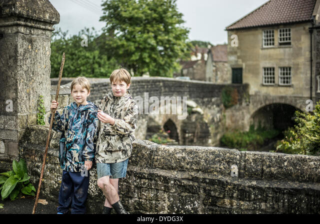 Two brothers stand next to the river Chew at Pensford Bridge in Somerset. - Stock Image