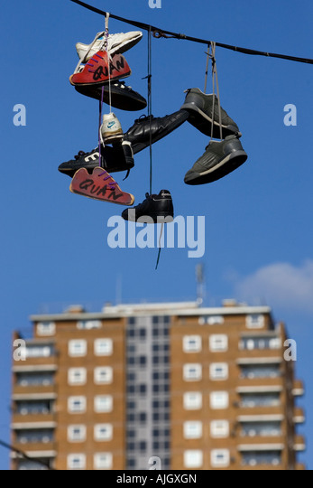 Five pairs of trainers hanging from a telephone line in the North Lanes, Kensington Street, Brighton, East Sussex, - Stock-Bilder