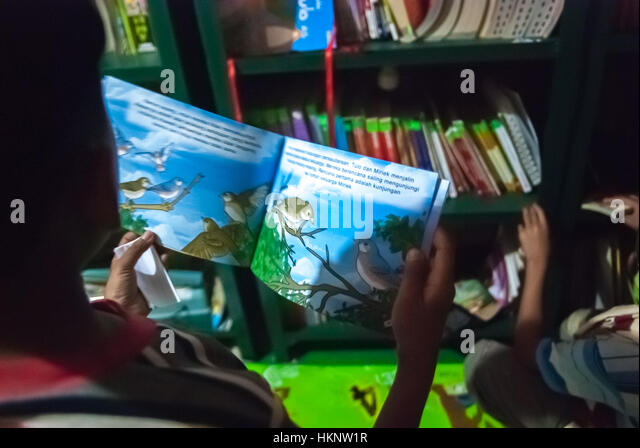 A boy reading illustrated book in a community library. © Reynold Sumayku - Stock Image