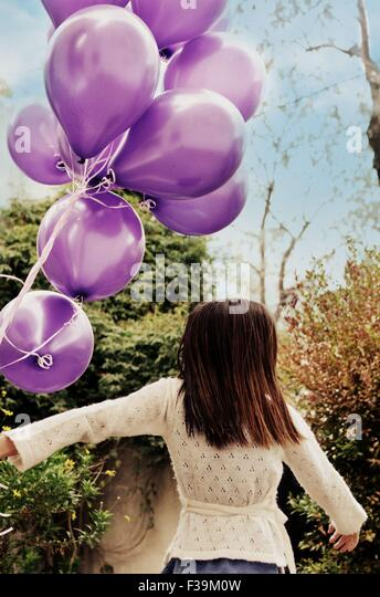 Rear view of a girl holding a bunch of purple balloons - Stock Image