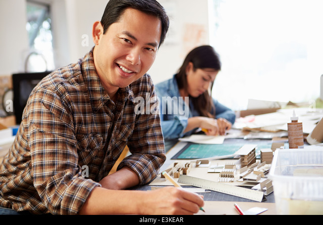 Male Architect Working On Model In Office - Stock Image