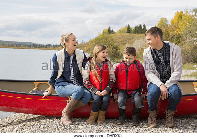 Happy family sitting together on canoe at lakeshore - Stock Image
