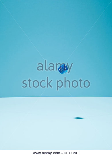 Blue dice in mid-air - Stock Image