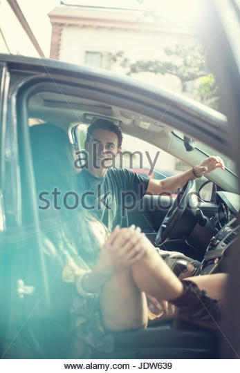 Young woman getting out of car, young man in driving seat - Stock-Bilder