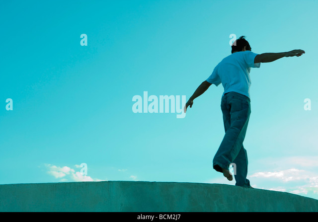 Man standing on one leg on ledge, arms out, low angle view - Stock Image