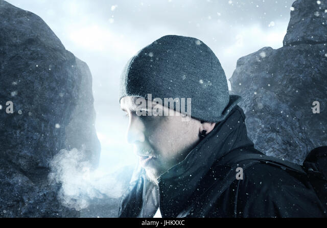 hiker breathe out in front of mountain landscape - Stock Image