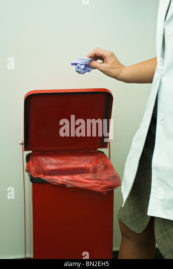 Discarding disposable latex glove in medical waste bin - Stock Image