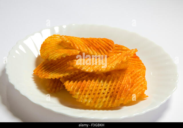 Junk food snacks salty and spicy potato chips or wafer served in plate