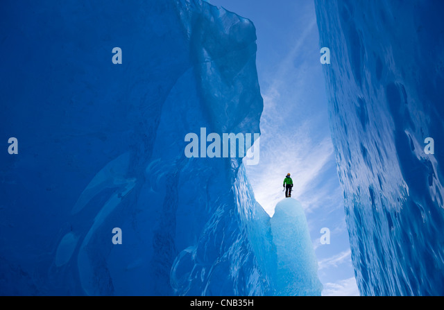 An ice climber surveys a wide crevasse from within Mendenhall Glacier, Juneau, Southeast Alaska, Winter - Stock Image