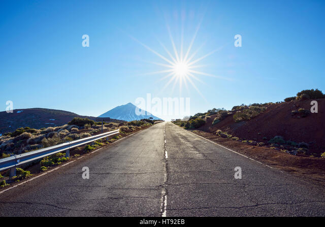 Road with Pico del Teide Mountain and Sun, Parque Nacional del Teide, Tenerife, Canary Islands, Spain - Stock Image