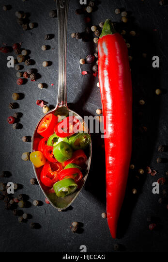Red hot pepper peperoni whole and chopped on a spoon with pepper and on black slate background. - Stock Image