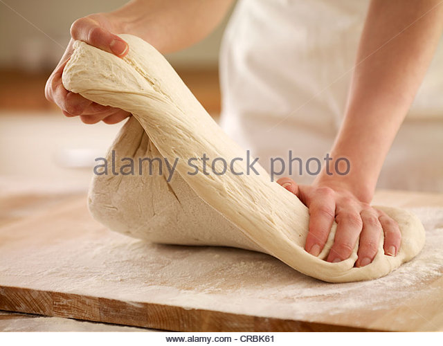 Woman kneading dough - Stock-Bilder