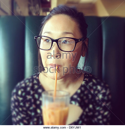 Korean woman drinking iced tea in cafe - Stock Image
