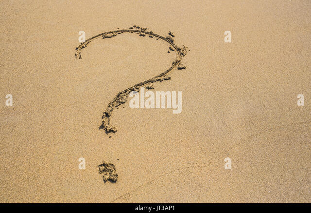 question mark drawn on the sand of a beach in summer - Stock Image