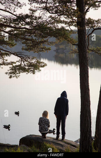 Sweden, Vastergotland, Harskogen, Stora Harsjon, Boy (12-13) and girl (10-11) by lake - Stock Image