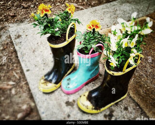 Flowers planted in children's boots - Stock-Bilder