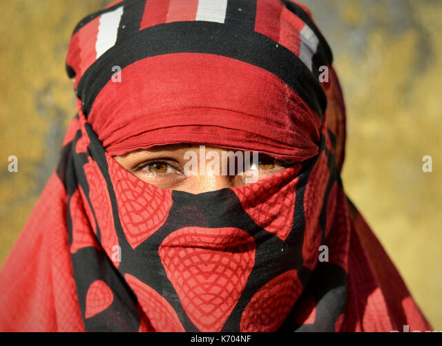 Young Indian woman with beautiful eyes, covering her hair and face with a trendy red-and-black headscarf; Junagadh, - Stock Image