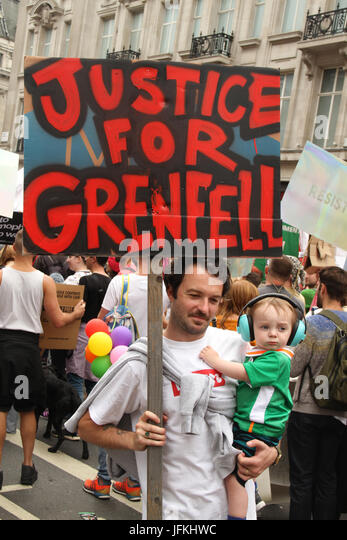 London, UK - 1 July 2017 - A Demonstrator with his young child holds a 'Justice for Grenfell'  in a national - Stock Image