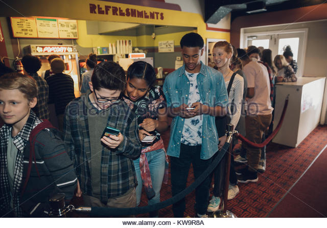 Tween boys and and girls texting with smart phones waiting in queue in movie theater lobby - Stock Image
